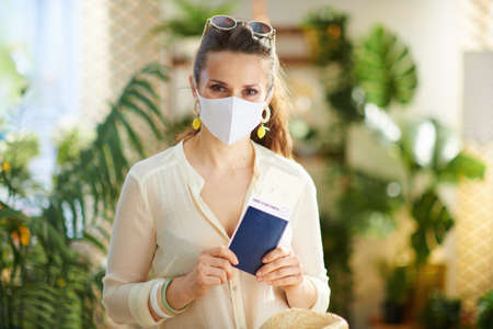 Travel during covid-19 pandemic. Seen from behind traveller woman with smartphone, covid passport app and medical mask in the house in sunny day.