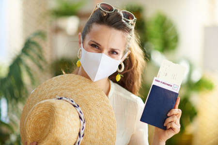 Travel during covid-19 pandemic. Seen from behind traveller woman with smartphone, covid passport app and medical mask in the house in sunny day. Zdjęcie Seryjne