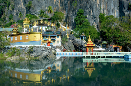 Bayin Nyi (Begyinni) Complex  in Hpa-An, Myanmar. Buddhist monastery and lots of golden stupas reflecting in the water of the sacred lake. Stock Photo
