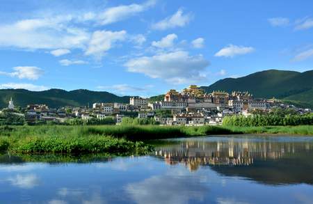 Songzanlin Tibetan Buddhist Monastery reflecting in the water of the sacred lake in Shangri-La, Yunnan province, China