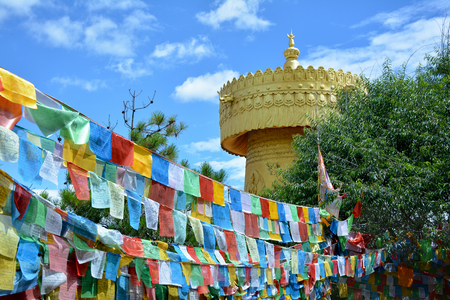 tibetian: Colorful tibetian flags and biggest buddhist wheel in the world on the background of blue sky in Shangri-La, China