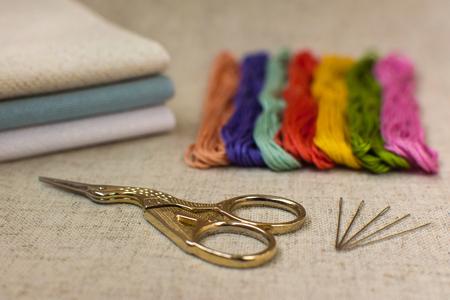 punto de cruz: Primer plano del bordado y el kit de punto de cruz en un fondo de lino natural. Tijeras, agujas, hilos de colores y lienzos.