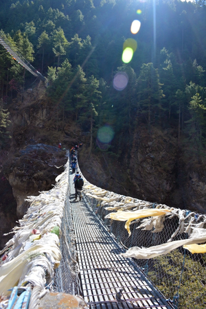 Group of tourists crossing high bridge in Himalayas, Nepal. Lots of fluttering tibetian prayer flags.  Stock Photo