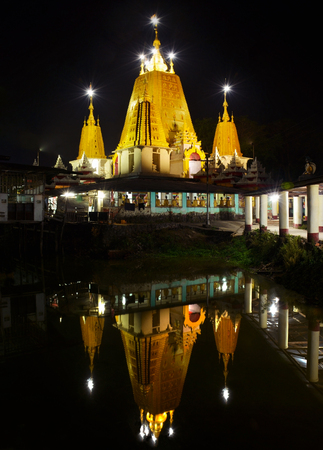 ye: Beautiful night view of the Ye Kyaung Buddhist Temple reflecting in  the water, Hpa-An city, Myanmar.