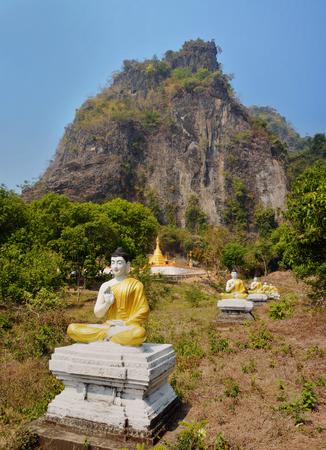 Row of sitting Buddha statues in Lumbini garden at the bottom of Mount Zwegabin, Hpa-An, Myanmar