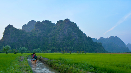 HPA-AN, MYANMAR - FEB 7, 2016 Burmese boatman driving the boat with pilgrims from Sadan Sin Min Cave in Hpa-An, Myanmar. Rice plantations and mountains on the background. Editorial