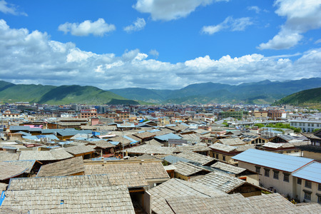 tibetian: Shangri-La (Zhongdian) city, Yunnan province, China. Wooden roofs of the tibetian houses on the foreground.
