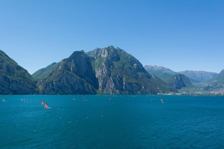 View of Riva Del Garda lakeshore with lots of windsurfers on the foreground Italy, Europe.