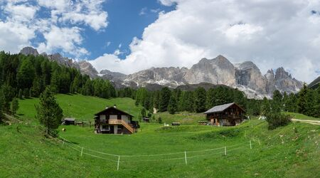 Panorama of Catinaccio (Rosengarten) massif and Vajolet Towers. Alpine wooden houses and grassland on the foreground