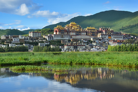 Ganden Songzanlin Complex reflecting in the lake. Shangri-La County, Yunnan province, China Sajtókép