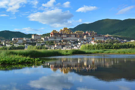 Beautiful view of the Ganden Sumtseling Temple reflecting in the water. Zhongdian (Shangri-La), China