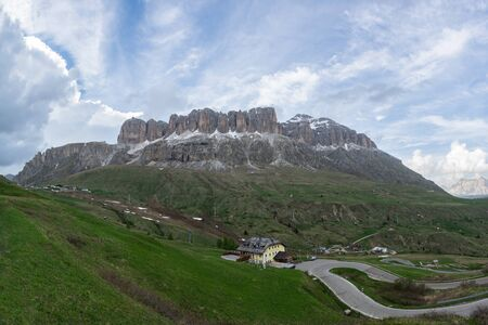 Panorama of Sella massif and Piz Boe. Mountain road with serpentine on the foreground