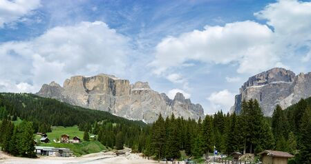 DOLOMITES, ITALY - JUNE 15, 2019 - Sellaronda Bike Day. Panoramic view at Sella massif and riding cyclists. Dolomites, Italy