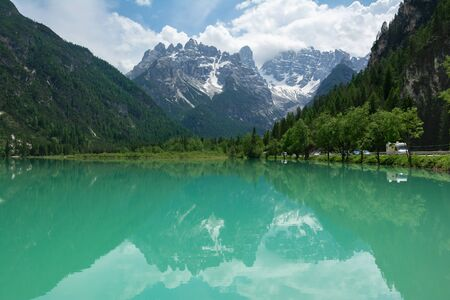 View of Lago Di Landro and surrounding mountains, Dolomites, Italy. Smooth surface of the lake with reflections.