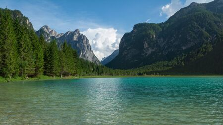 View of Dobbiaco Lake and surrounding mountains. Dolomites, Italy 写真素材 - 129461794