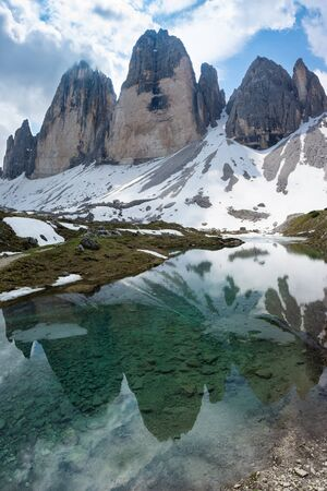 Beautiful view of Tre Cime di Lavaredo reflecting in the water. Dolomites, Italy.