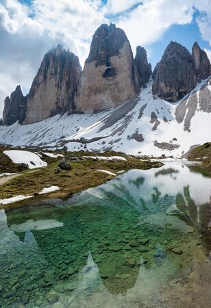 Reflections of Tre Cime (Drei Zinnen) mountain in the water of alpine lake. South Tyrol, Italy
