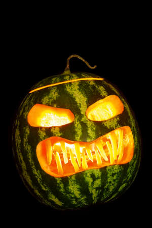 Traditional jack-o-lantern made from a watermelon, lit from within by a candle. Halloween decoration.