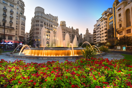 Valencia, Spain - August 01, 2016: The city hall at dusk, with flowers, its majestic fountain and the historic buildings in the background