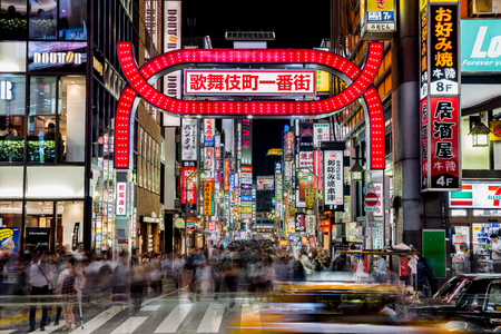 Tokyo, Japan - October 21, 2016: Night life in Kabukicho, the entertainment and red-light district in Shinjuku. The popular Kabukicho sign with billboars, traffic and people flow taken with a long exposure effect