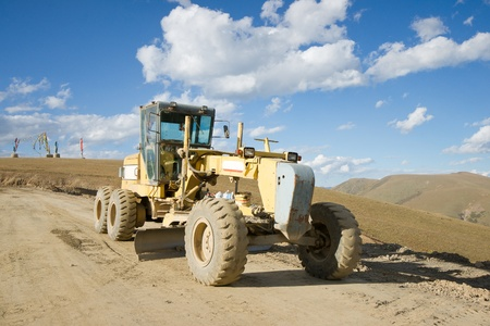 unsurfaced road: Road building machine with highland landscape