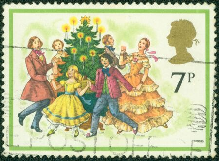 UNITED KINGDOM - CIRCA 1978  A stamp printed in England shows Carolers Around Christmas Tree, circa 1978 photo