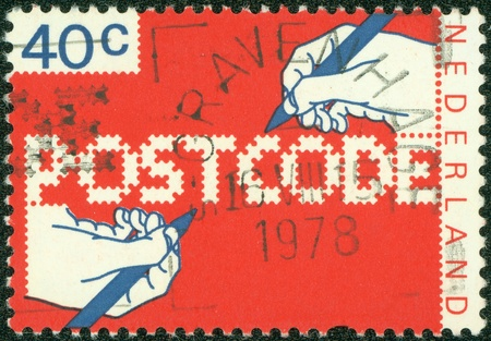 specular: NETHERLANDS - CIRCA 1978  A stamp printed in the Netherlands, dedicated to the Introduction of new postal code, shows the hand of a writing text, circa 1978