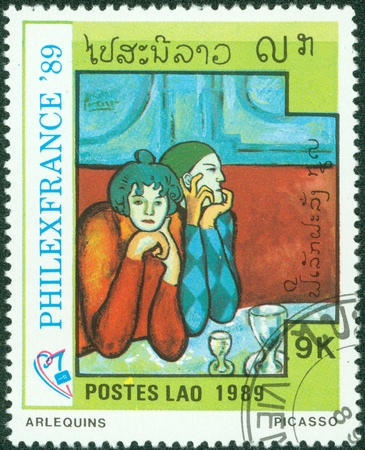 quo: LAOS-CIRCA 1989  A stamp printed in the Laos shows painting  arlequins  ;quo t; by Pablo Picasso, circa 1989