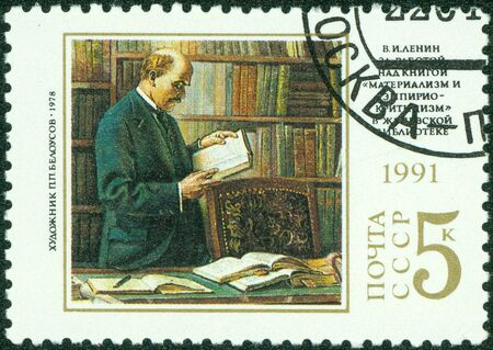 franked: USSR - CIRCA 1991  A stamp printed in USSR commemorating the 121st anniversary of Lenin s birth  He is shown in a library researching through several books, circa 1991  Stock Photo