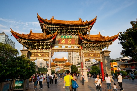 KUNMING, YUNNAN - August 17  People walk under the Golden Horse Memorial Archway JinMaBiJi fang  on August 17, 2012 in Kunming of Yunnan Province