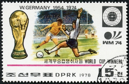 NORTH KOREA - CIRCA 1978  A Stamp printed in NORTH KOREA shows the Soccer players, Cup, Emblem and Globe, Germany  1954, 1974 , World Cup Winners, circa 1978 報道画像