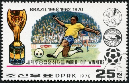 NORTH KOREA - CIRCA 1978  A Stamp printed in NORTH KOREA shows the Soccer players, Cup, Emblem and Globe, Brazil  1958,1962,1970 , World Cup Winners, circa 1978 Stock Photo - 17614976