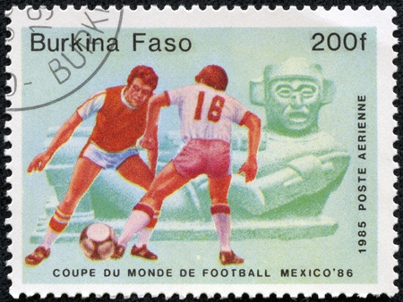BURKINA FASO - CIRCA 1986  stamp printed by Burkina Faso, shows soccer players and ball  Championships Mexico, circa 1986  Stock Photo - 17554716