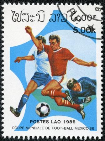 LAOS - alrededor de 1986 Un sello impreso en LAOS muestra a los jugadores de fútbol en el campo de fútbol, ??con la inscripción y el nombre de la serie de la Copa Mundial de Fútbol de la UEFA, México - 1986, alrededor del año 1986 Foto de archivo - 17615009