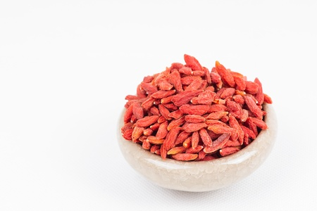 dried wolfberry fruit in bowl on white background photo