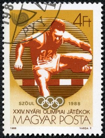 deportes olimpicos: Hungría - CIRCA 1988 Un sello impreso en Hungría muestra Vallas y emblema olímpico, con la inscripción y el nombre de los Juegos Olímpicos de serie en Seúl, 1988, alrededor de 1988