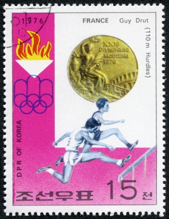 hurdling: KOREA - CIRCA 1976  stamp printed in North Korea, shows Gold Medal, emblem of Games, with inscription  Hurdling, Guy Drut, France , from series  Summer Olympic Games 1976, Medal Winners , circa 1976