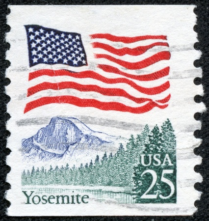 UNITED STATES OF AMERICA - CIRCA 1988  a stamp printed in the USA shows USA Flag over Yosemite Valley, circa 1988 photo