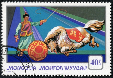 circuses: MONGOLIA - CIRCA 1974  A stamp printed in Mongolia shows a performing yak pushing a ball with a circus trainer, part of a series on Mongolian circuses, circa 1974