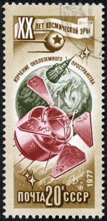 space age: RUSSIA - CIRCA 1977  Stamp printed in USSR  Russia , shows globe and sputniks, with inscription and name of series  20 years of a space age , circa 1977 Editorial