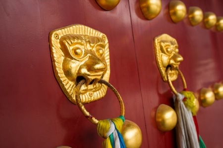 ancient red doors with gilded studs and lion head door knockers Stock Photo - 22186401