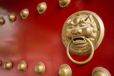 ancient red doors with gilded studs and lion head door knockers photo