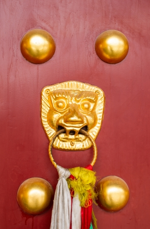 ancient red doors with gilded studs and lion head door knockers Stock Photo - 22978845