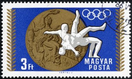 deportes olimpicos: Hungría - CIRCA 1969 sello impreso por Hungría, muestra la medalla olímpica y lucha libre, alrededor de 1969