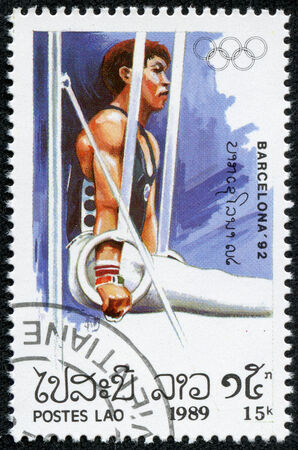 LAOS - CIRCA 1989  A stamp printed in Laos shows gymnast on the rings, series Olympic Games in Barcelona 1992, circa 1989