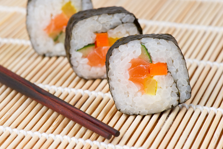 sushi with salmon and cucumber on bamboo mat with chopsticks photo