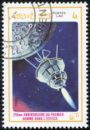 LAOS - CIRCA 1986  A stamp printed in Laos from the  25th anniversary of First Man in Space   issue shows satilite, circa 1986