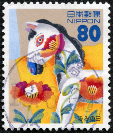 JAPAN - CIRCA 1996  A stamp printed in Japan commemorating National Letter Writing Day with a letter on top of tulip and a wildly decorated wooden horse, circa 1996