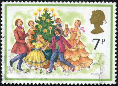 UNITED KINGDOM - CIRCA 1978  A stamp printed in United Kingdom from the  Christmas  Carol singing   issue shows Singing Carols round the Christmas Tree, circa 1978  Editorial