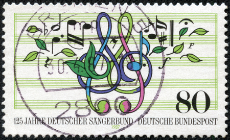 choral: GERMANY - CIRCA 1987  A stamp printed in Germany, is dedicated to the 125th anniversary of German Choral Society, shows musical notes, treble clef, leaves, circa 1987 Editorial